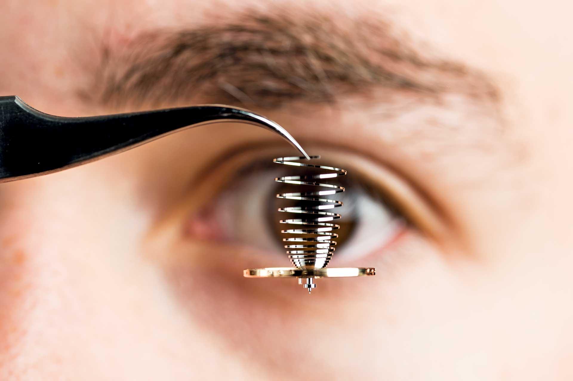Wichtigstes Hilfsmittel bei der Bearbeitung von Unruh und Unruhspirale: das menschliche Auge. Nur erfahrene Mitarbeiter können Unregelmäßigkeiten erkennen und ausgleichen.